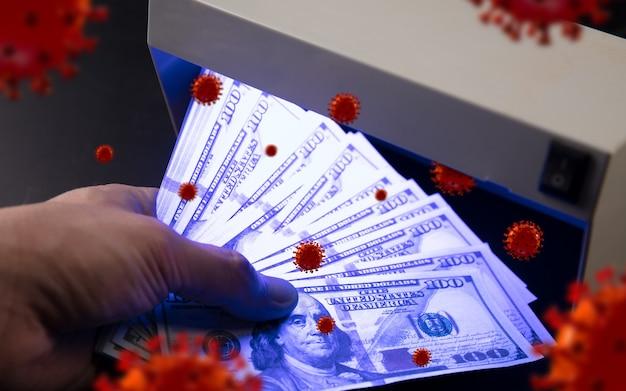 Męskie dłonie sprawdzają banknoty w detektorze, wokół krążą modele 3d koronawirusa. wysokie ryzyko infekcji. pandemia, epidemia, choroby i choroby, których nie widzimy na co dzień.