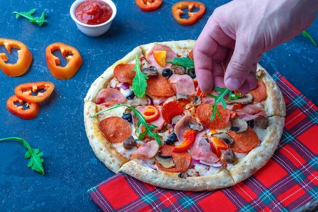 Męskie dłonie (szef kuchni) dekorują pizzę zielenią.