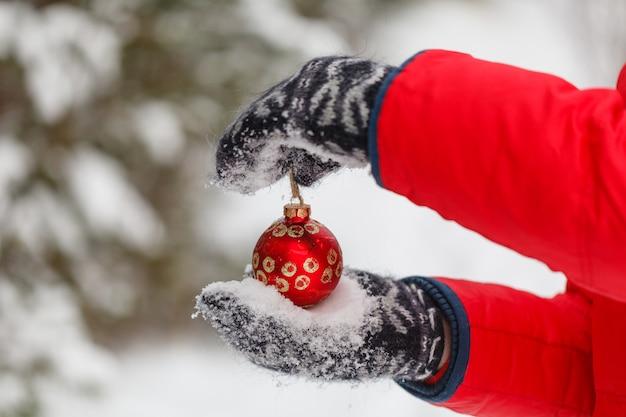 Męskie dłonie trzyma czerwoną piłkę bożego narodzenia. mroźny zimowy dzień w śnieżnym lesie. wesołych świąt i szczęśliwego nowego roku