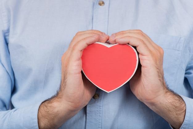 Męskie dłonie trzyma czerwone pudełko w kształcie serca. prezent dla ukochanej.