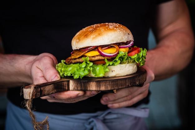 Męskie dłonie trzyma soczystego smacznego cheeseburgera z wołowiną, sałatą, ogórkami, pomidorem i krążkami cebuli na drewnianym stole. klasyczne jedzenie uliczne - burger z grilla