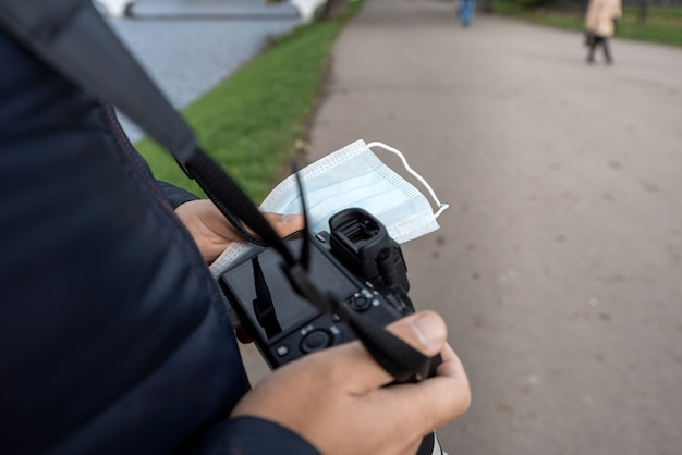 Męskie dłonie trzymają cyfrową lustrzankę i maskę medyczną