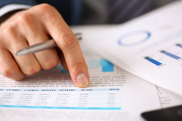 Męskie dłonie trzymają dokumenty ze statystykami finansowymi
