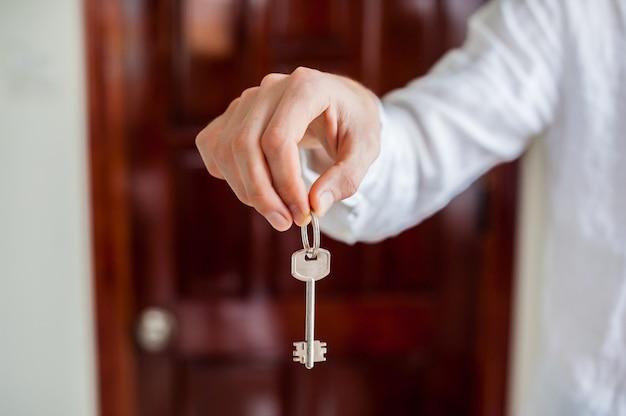 Męskie dłonie trzymają klucz od domu na tle drewnianych drzwi. posiadanie koncepcji nieruchomości