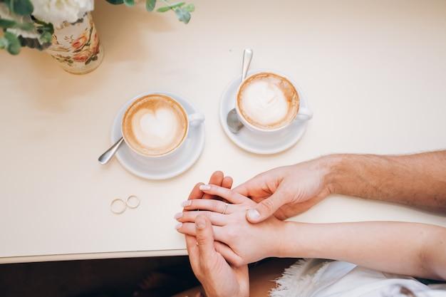 Męskie dłonie trzymają kobiece dłonie. ręka z obrączką. niezawodne męskie dłonie. silne męskie dłonie.