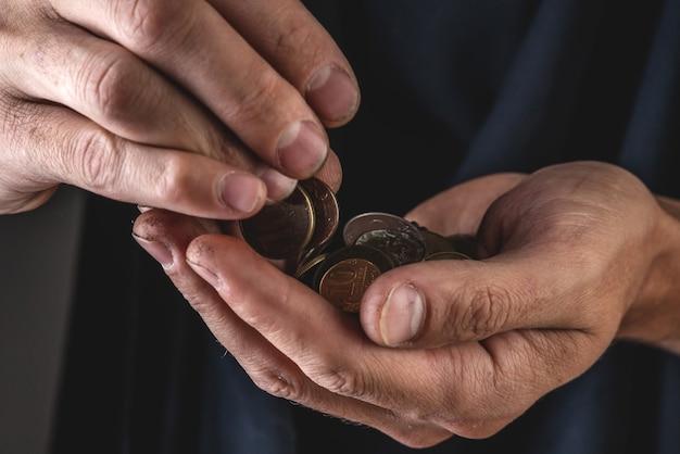 Męskie dłonie trzymają monety rubla z bliska na ciemnym tle