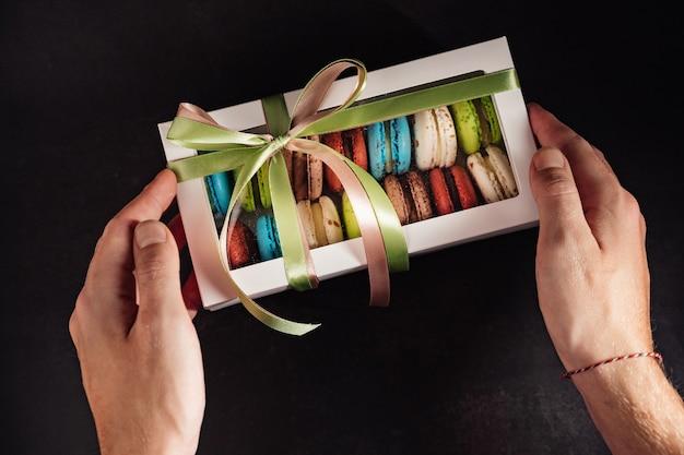 Męskie dłonie trzymają pudełko ciastek makaronikowych, prezent dla kobiety, którą kocha