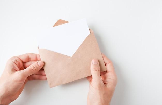 Męskie dłonie trzymające otwartą kopertę kraft z białą pustą kopią miejsca widok z góry