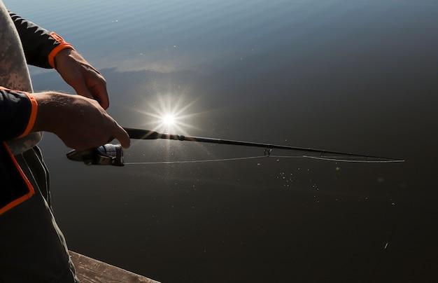 Męskie dłonie trzymające wędkę zbliżenie nad rzeką lub jeziorem z odbiciem promieni słonecznych