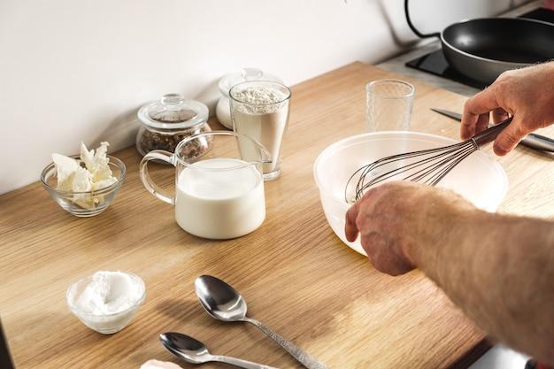 Męskie dłonie ugniatają ciasto trzepaczką na talerzu