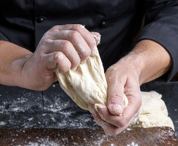 Męskie dłonie ugniatają ciasto z białej mąki pszennej