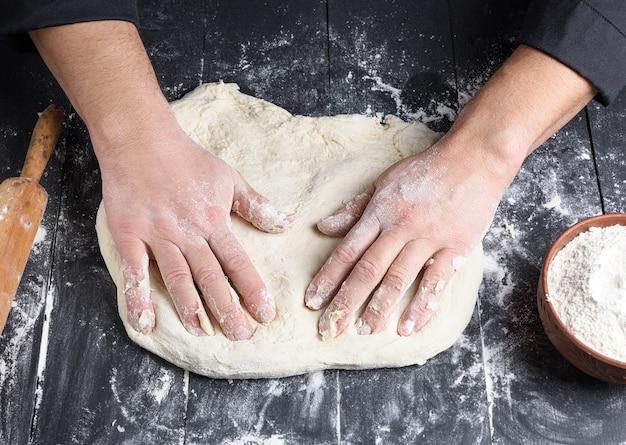 Męskie dłonie ugniatają okrągły kawałek ciasta do robienia pizzy