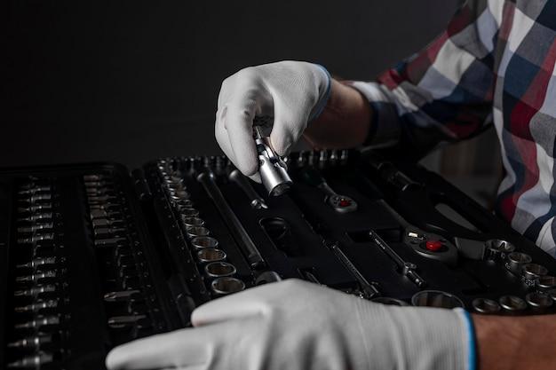 Męskie dłonie w białych rękawiczkach nad otwartym zestawem narzędzi z metalowych narzędzi do naprawy samochodu i domu, z bliska.