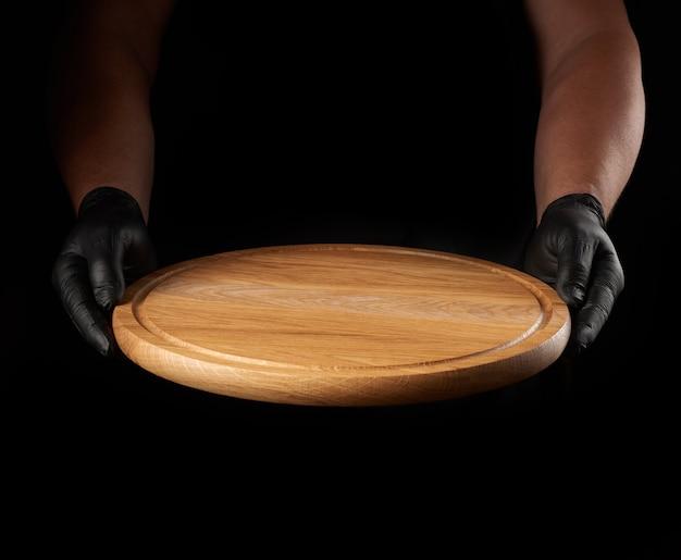 Męskie dłonie w czarnych rękawiczkach lateksowych trzyma okrągłą pustą drewnianą deskę do pizzy