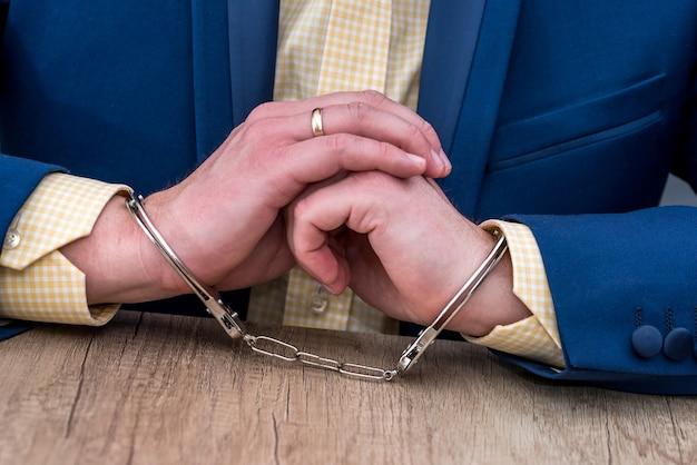 Męskie dłonie w kajdankach na drewnianym stole