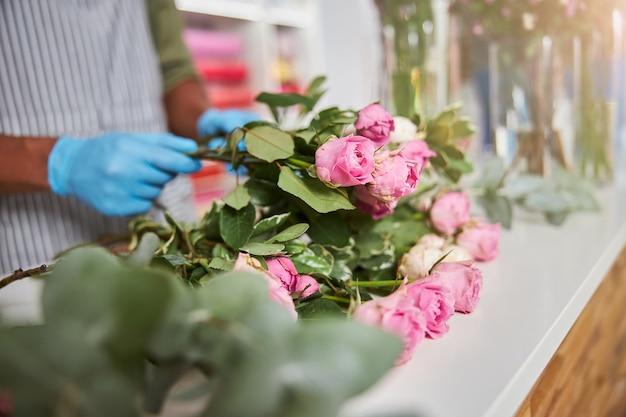 Męskie dłonie w lateksowych rękawiczkach podczas robienia bukietów świeżych kwiatów w sklepie