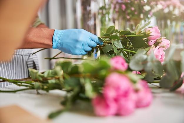 Męskie dłonie w lateksowych rękawiczkach robiące bukiet świeżych kwiatów podczas dnia pracy w sklepie