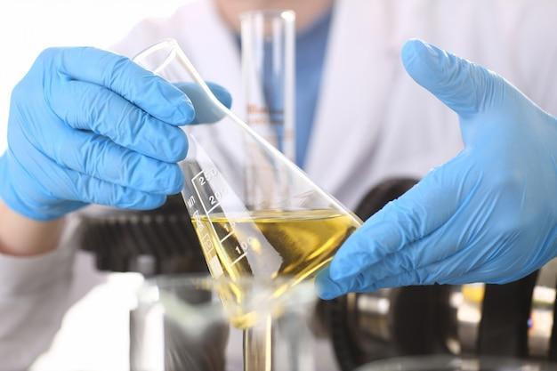 Męskie dłonie w rękawicach ochronnych trzymają probówkę w dłoniach, przeprowadzając test chemiczny automatycznej skrzyni biegów z olejem silnikowym i wzmacniacza hydraulicznego