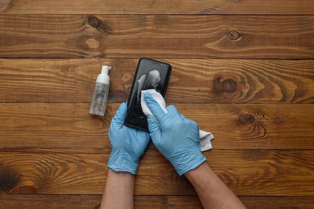 Męskie dłonie w rękawiczkach medycznych traktują telefon antyseptycznie.