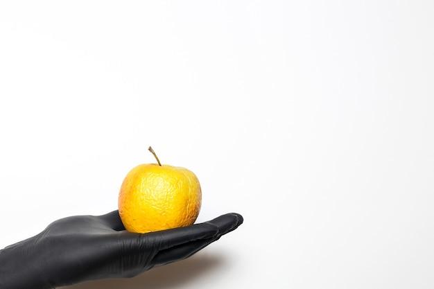 Męskie dłonie w rękawiczkach medycznych z pomarszczonymi jabłkami i strzykawką w rękach na białym