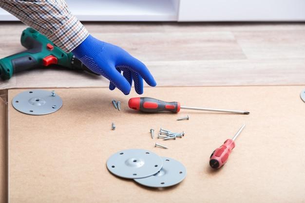 Męskie dłonie w rękawiczkach, mistrz zbiera meble stołowe za pomocą narzędzi śrubokręt, instrument w domu. montaż mebli za pomocą śrubokręta. przeprowadzki, majsterkowanie, naprawa i renowacja mebli.