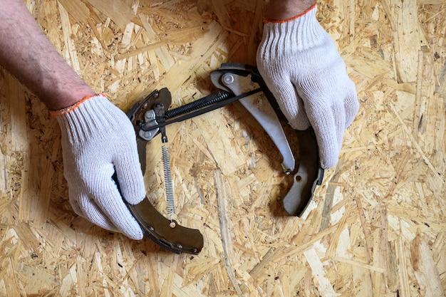 Męskie dłonie w rękawiczkach to uchwyty hamulca bębnowego samochodu zdemontowane na tle arkusza sklejki osb. leżał płasko, widok z góry