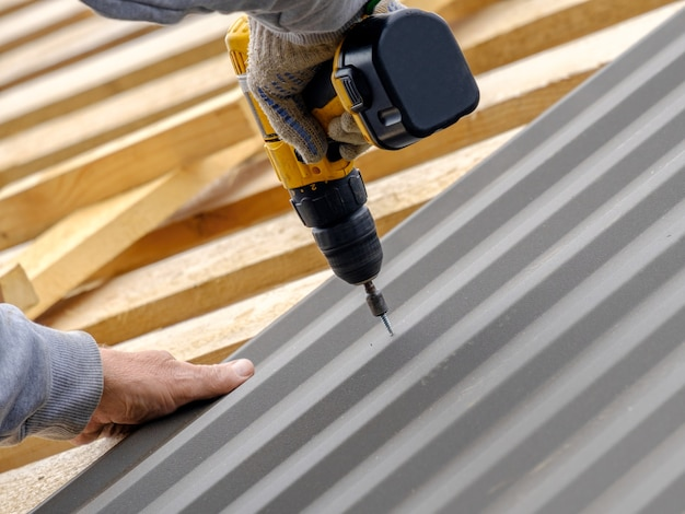 Męskie dłonie w rękawiczkach ze śrubokrętem przykręcają blachodachówkę do dachu