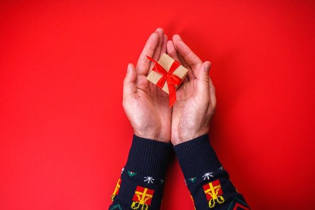 Męskie dłonie w świątecznym swetrze z prezentem na czerwono.
