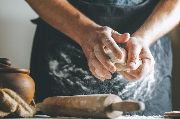 Męskie dłonie wyrabiają ciasto z mąką obok glinianego garnka i butelki oleju i wałka do ciasta na ciemnym stole podczas gotowania