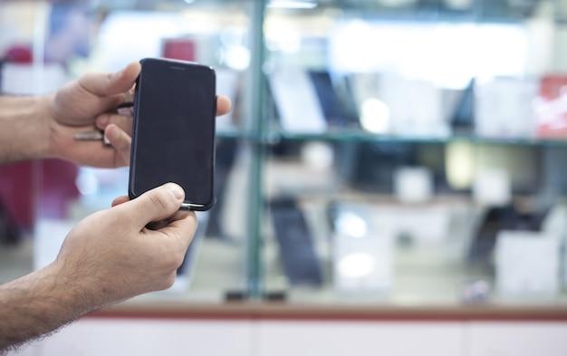 Męskie dłonie wyświetlono smartfona w sklepie elektronicznym.