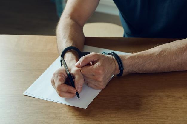 Męskie dłonie z kajdankami wypełniają policyjny rejestr, przyznanie się. na szczycie policji śledczej