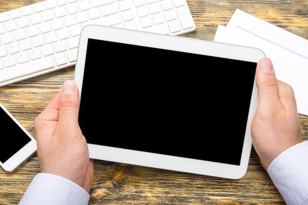 Męskie dłonie z komputerem typu tablet, telefonem i klawiaturą na stole biurowym