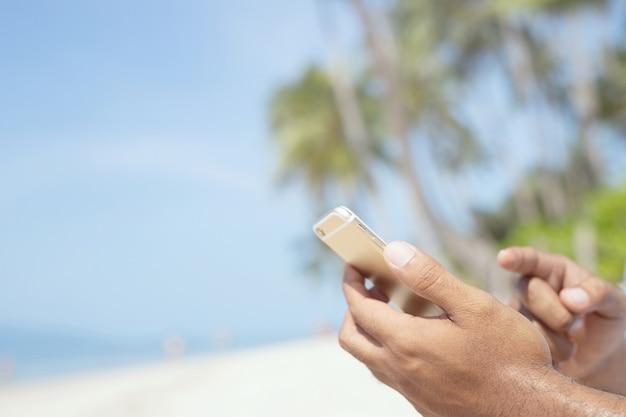 Męskie dłonie z mobilnym smartfonem podczas wakacji na tropikalnej plaży.