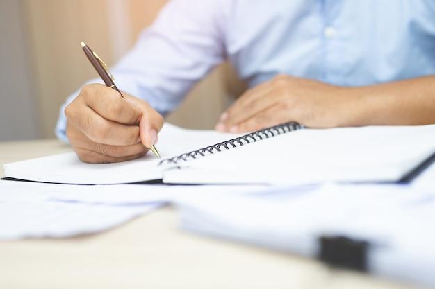 Męskie dłonie z piórem, pisanie na notebooku