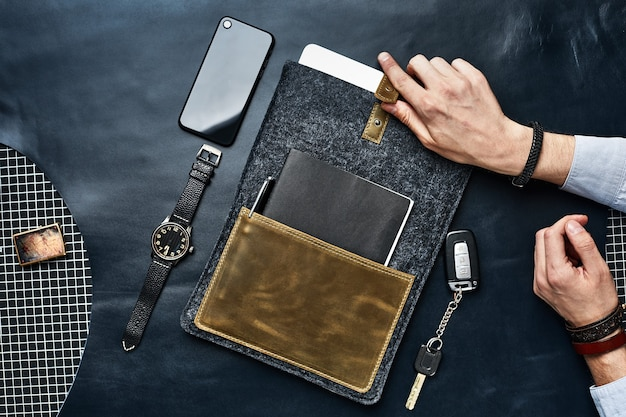 Męskie dłonie z ręcznie robioną pokrowcem na laptopa, rozłożone dookoła, kluczyki do samochodu, zegarek, smartfon, nowoczesne akcesoria na całe życie, styl życia.