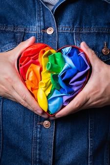 Męskie dłonie z tęczową flagą lgbtq w kształcie serca z dumą miesiąca