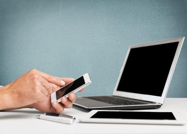 Męskie dłonie z telefonem na laptopie na biurowym stole