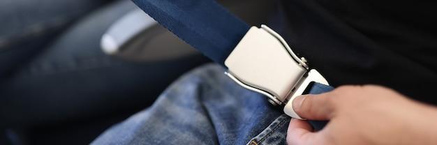 Męskie dłonie zapinające pasy na zbliżenie samolotu
