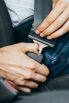Męskie dłonie zapinające pasy w samochodzie
