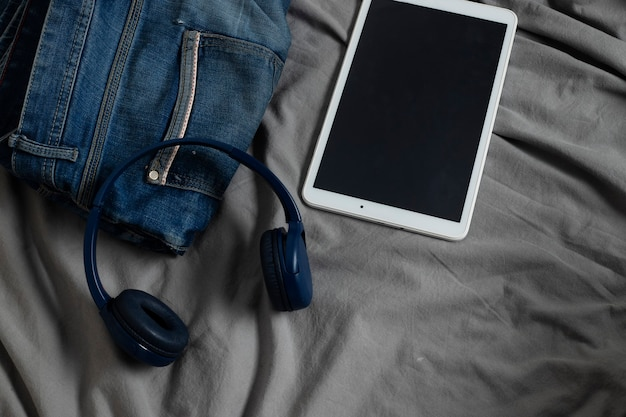Męskie dżinsy na łóżku obok słuchawek i tabletu