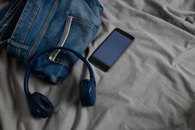 Męskie dżinsy na łóżku obok słuchawek i telefonu komórkowego