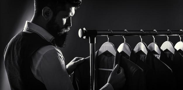 Męskie garnitury wiszące w rzędzie. odzież męska, butiki. krawiec, krawiectwo. stylowy garnitur męski. mężczyzna garnitur, krawiec w swoim warsztacie. przystojny brodaty mężczyzna moda w klasycznym kostiumie. czarny i biały.