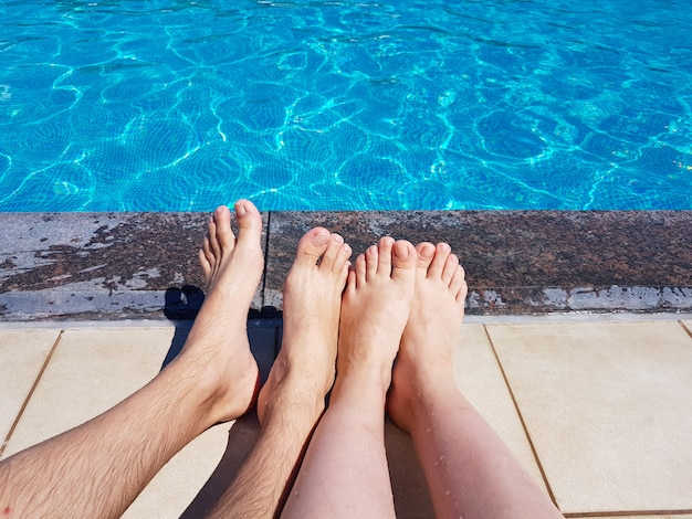 Męskie i damskie stopy przy basenie na niebieskim tle wody w letni dzień. odpoczywaj, podróżuj