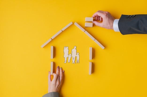 Męskie i kobiece dłonie budują dom z drewnianych klocków, aby schronić wyciętą z papieru sylwetkę rodziny.