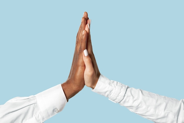 Męskie i kobiece dłonie dotykając na białym tle na niebiesko.