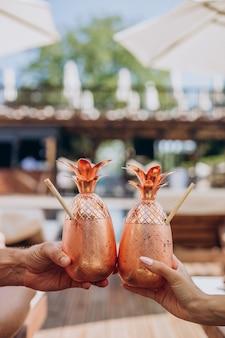 Męskie i kobiece dłonie trzymające koktajle przy basenie