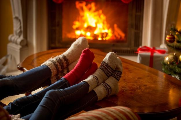 Męskie i kobiece stopy w wełnianych skarpetkach ogrzewają się przy płonącym kominku
