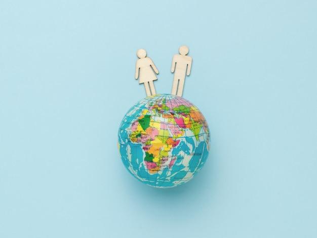 Męskie i żeńskie drewniane figurki na modelu kuli ziemskiej na niebieskim tle.