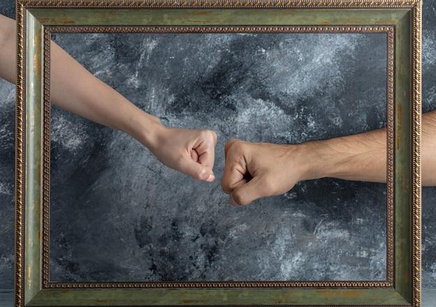 Męskie i żeńskie pięści spotykają się na środku ramy obrazu.