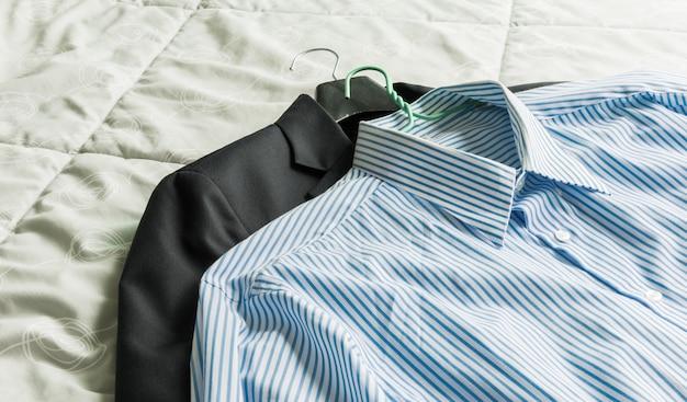 Męskie klasyczne koszule i garnitur na łóżku